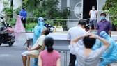 """Nhân viên y tế lấy mẫu xét nghiệm cộng đồng người dân trong khu vực """"vùng xanh"""" phường Phước Long, TP Nha Trang. Ảnh: QUỲNH ANH"""