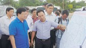 Phó Thủ tướng Trịnh Đình Dũng nghe báo cáo về dự án xây dựng cầu Đại Ngãi. Ảnh: MINH LUÂN