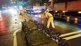 Cảnh sát giao thông hỗ trợ công nhân vệ sinh thu dọn vỏ chai đổ trên đường