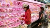 Consumers buy pork at a supermarket. (Photo: SGGP)