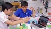 """Anh Trần Mai Khiêm - cử nhân tài năng CNTT khóa 2016 và Hoàng Trung Hiếu (bên phải) - cử nhân tài năng CNTT khóa 2015 đang nghiên cứu hoàn thành dự án """"Điều khiển đèn giao thông thông minh"""" qua camera. Ảnh: HOÀNG HÙNG"""