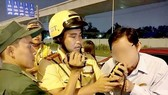 A traffic police officer measures breath alcohol concentration of a driver. (Photo: Sggp)