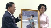 Chairman of the Lao Front for National Construction – Vientiane chapter Bounthieng Khounsy (L) presents a picture to To Thi Bich Chau, Vice President of the Vietnam Fatherland Front – Ho Chi Minh City chapter (Source: daidoanket.vn)