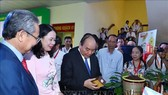 Prime Minister Nguyen Xuan Phuc visits an exhibition within the conference. (Photo: VNA)