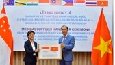 Singaporean Ambassador Catherine Wong Siow Ping (left) receives a donation of Reverse Transcription Polymerase Chain Reaction test kits from Vietnamese Deputy Foreign Minister Nguyen Quoc Dung in May.
