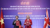 Minister of Industry and Trade Tran Tuan Anh and UK Secretary of State for International Trade Liz Truss sign the agreed minutes on the conclusion of negotiations over the UK-Vietnam Free Trade Agreement on December 11. (Photo: VNA)