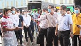 HCMC People's Committee Vice Chairman Duong Anh Duc leads a delegation to inspect the epidemic prevention and control at Binh Dien whosale market. (Photo: SGGP)
