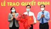Standing Deputy Secretary of HCMC's Party Committee Phan Van Mai (R) and Vice chairwoman of the municipal People's Committee, Phan Thi Thang (L) congratulate Mr. Vu Anh Khoa. (Photo: SGGP)