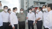 Prime Minister Pham Minh Chinh (C) inspects the epidemic prevention and control at a quarantine facility in the dormitory of the Vietnam National University HCMC. (Photo: SGGP)