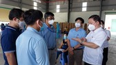 HCMC People's Committee Vice Chairman Duong Anh Duc (R) inspects the Covid-19 vaccination at the Nam Anh Production and Trade Company in the Tan Tao Industrial Zone in Binh Tan District. (Photo: SGGP)