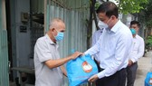 Vice Chairman of the HCMC People's Committee Le Hoa Binh (R) present gift to a resident in a green zone in Vinh Loc B Commune. (Photo: SGGP)