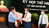 Secretary of the Party Committee of HCMC Nguyen Van Nen (C) and Mr. Nguyen Thanh Phong (R) offer flowers to Mr. Phan Van Mai. (Photo: SGGP)