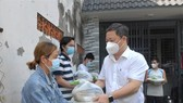Vice chairman of the HCMC People's Committee Duong Anh Duc offers gifts to local people in Ba Diem Commune. (Photo: SGGP)