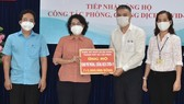 Chairwoman of the Vietnam Fatherland Front of HCMC, To Thi Bich Chau receives a cash assistance of the Party Committee of the banking sector in HCMC . (Photo: SGGP)