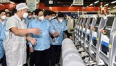 Prime Minister Pham Minh Chinh (second from left) visits the factory of the Samsung Electronics Vietnam Co. Ltd in Thai Nguyen province. (Photo: VNA)