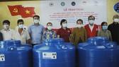 Phu nhân nguyên Chủ tịch nước Trương Tấn Sang (từ trái qua, người thứ 5) trao tặng 100 bồn chứa nước ngọt cho bà con nghèo tại xã Nam Thái A. Ảnh: TÍN HUY