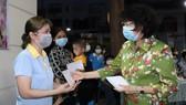 Đồng chí Tô Thị Bích Châu, Chủ tịch Ủy ban MTTQ Việt Nam TPHCM trao quà nữ công nhân khó khăn tối 4-2
