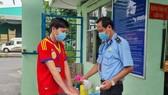 Công nhân thực hiện khử khuẩn và đo thân nhiệt trước khi vào làm việc tại doanh nghiệp trên địa bàn TPHCM