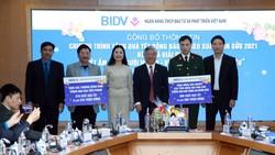 Đại diện BIDV trao bảng tượng trưng cho các đơn vị để tặng quà Tết cho người nghèo