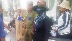 Bà Lê Thị Lại (che mặt) bị một số người chơi hụi phát hiện khi đang giao dịch tại một công ty bảo hiểm