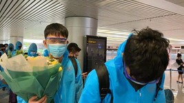 Midfielder Luong Xuan Truong (L) receives flowers from Vietnamese fans at the airport. (Photo: SGGP)