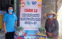第十一郡第二坊婦女會主席林玉明(左)將民生必需品交給貧困者。