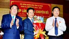 Bí thư Tỉnh ủy Cà Mau Nguyễn Tiến Hải (phải) và Chủ tịch HĐND tỉnh, ông Trần Văn Hiện (trái) tặng hoa chúc mừng tân Chủ tịch UBND tỉnh, ông Lê Quân