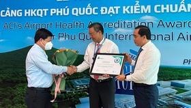 Ông Tống Phước Trường, Bí thư Thành uỷ Phú Quốc (bìa trái) và ông Huỳnh Quang Hưng, Chủ tịch UBND TP Phú Quốc (bìa phải) trao hoa và giấy chứng nhận cho đại diện Cảng HKQT Phú Quốc