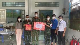 Phó Bí thư Thường trực Đảng ủy Tổng Công ty Điện lực TPHCM Bùi Hải Thành (bìa phải) thăm và tặng quà các y bác sĩ, nhân viên Trạm y tế lưu động số 12 tại xã Đa Phước, huyện Bình Chánh