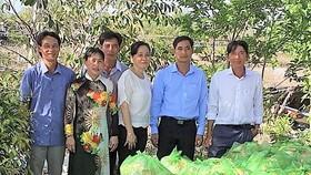Ông Trần Tấn Nhanh và đại diện địa phương trao quà nhu yếu phẩm cho bà con