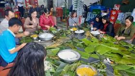 Người dân TP Vinh (Nghệ An) gói bánh chưng chuyển vào ủng hộ đồng bào bị lũ lụt. Ảnh: TRẦN TRUNG HIẾU