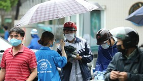 Thí sinh đội mưa đến điểm thi. Ảnh: QUANG PHÚC