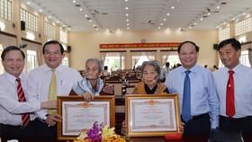 Phó Bí thư Thường trực Thành ủy TPHCM Tất Thành Cang trao danh hiệu Bà mẹ Việt Nam anh hùng cho mẹ Nguyễn Thị Rực và mẹ Nguyễn Thị Sáu. Ảnh: VIỆT DŨNG