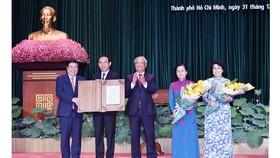 Phó Chủ tịch Quốc hội Uông Chu Lưu trao Nghị quyết của Ủy ban Thường vụ Quốc hội về việc sắp xếp các đơn vị hành chính cấp huyện, cấp xã và thành lập TP Thủ Đức thuộc TPHCM cho lãnh đạo TPHCM. Ảnh: VIỆT DŨNG