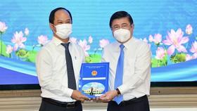 Chủ tịch UBND TPHCM Nguyễn Thành Phong trao quyết định cho Đồng chí Lê Đức Thanh. Ảnh: VIỆT DŨNG