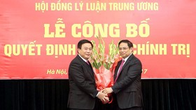 Đồng chí Phạm Minh Chính, Ủy viên Bộ Chính trị, Bí thư Trung ương Đảng, Trưởng ban Tổ chức Trung ương trao Quyết định của Bộ Chính trị và tặng hoa cho đồng chí Nguyễn Xuân Thắng. Ảnh: TTXVN