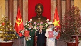 Tổng Bí thư, Chủ tịch nước Nguyễn Phú Trọng trao quyết định phong quân hàm Đại tướng và tặng hoa chúc mừng các đồng chí Tô Lâm, Lương Cường. Ảnh TTXVN