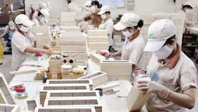Workers are processing wooden products for export (photo: SGGP)