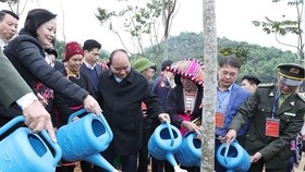 Prime Minister Nguyen Xuan Phuc (second from left) waters a tree after growing it as part of a tree-planting campaign launched in northern Yen Bai Province on Thursday (Photo: VNA)
