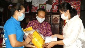 Deputy Editor-in-chief Ly Viet Trung (1st, R) presents gifts to poor laborers (Photo: SGGP)