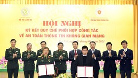 Lieutenant General Dinh The Cuong and Head of AIS Nguyen Thanh Phuc are signing the Regulation. (Photo: SGGP)