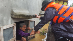 A rescue worker take an old woman out from her flooded house in Quang Binh Province (Photo: SGGP)