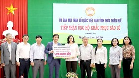 Deputy Chairwoman of the Municipal People's Council Phan Thi Thang hands over more than VND5.7 billion (US$ 245,643) to people affected by recent floods and storms in Thua Thien- Hue Province