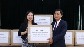 Trinh Thi Tam (L) from the Vietnamese Embassy symbolically hands over face masks to Vice Chairman of the General Association of Vietnamese People in Laos Pham Van Hung on November 28 (Photo: VNA)