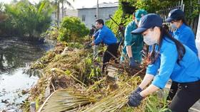 Thanh niên TPHCM tham gia dọn vệ sinh trên rạch Cây Me, quận 7 trong Ngày Chủ nhật xanh. Ảnh: VIỆT DŨNG