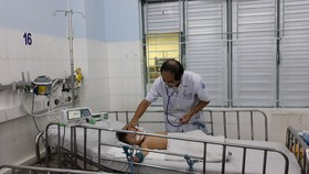 PGS TS Phạm Văn Quang, Trưởng Khoa Hồi sức tích cực chống độc BV Nhi Đồng 1 đang khám cho bệnh nhi