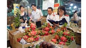 Đoàn kiểm tra nguồn gốc xuất xứ trái cây nhập vào chợ. Ảnh: HOÀNG HÙNG