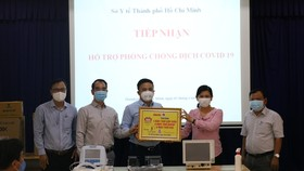 """Đại diện Báo Tuổi Trẻ trao tặng quà, tiền mặt hỗ trợ chương trình """"Cùng Tuổi Trẻ chống dịch Covid-19"""" cho Sở Y tế TPHCM.  Ảnh: HOÀNG AN"""