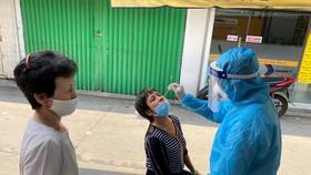 Nhân viên y tế lấy mẫu xét nghiệm cho người dân ở khu vực đường Cao Thắng, phường 17, quận Phú Nhuận, TPHCM. Ảnh: CAO THĂNG