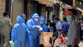 Nhân viên y tế lấy mẫu các trường hợp tiếp xúc gần ca mắc Covid-19 bán quán ăn ở quận 3, TPHCM, ngày 20-5-2021.Ảnh: CAO THĂNG